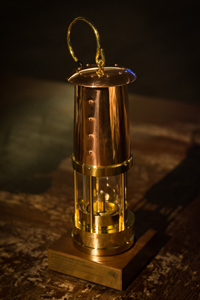 A brass miner's lamp sits on a wood table