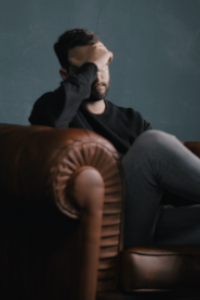 A man sits in an arm chair with his hand covering his face. His expression looks sad and anxious